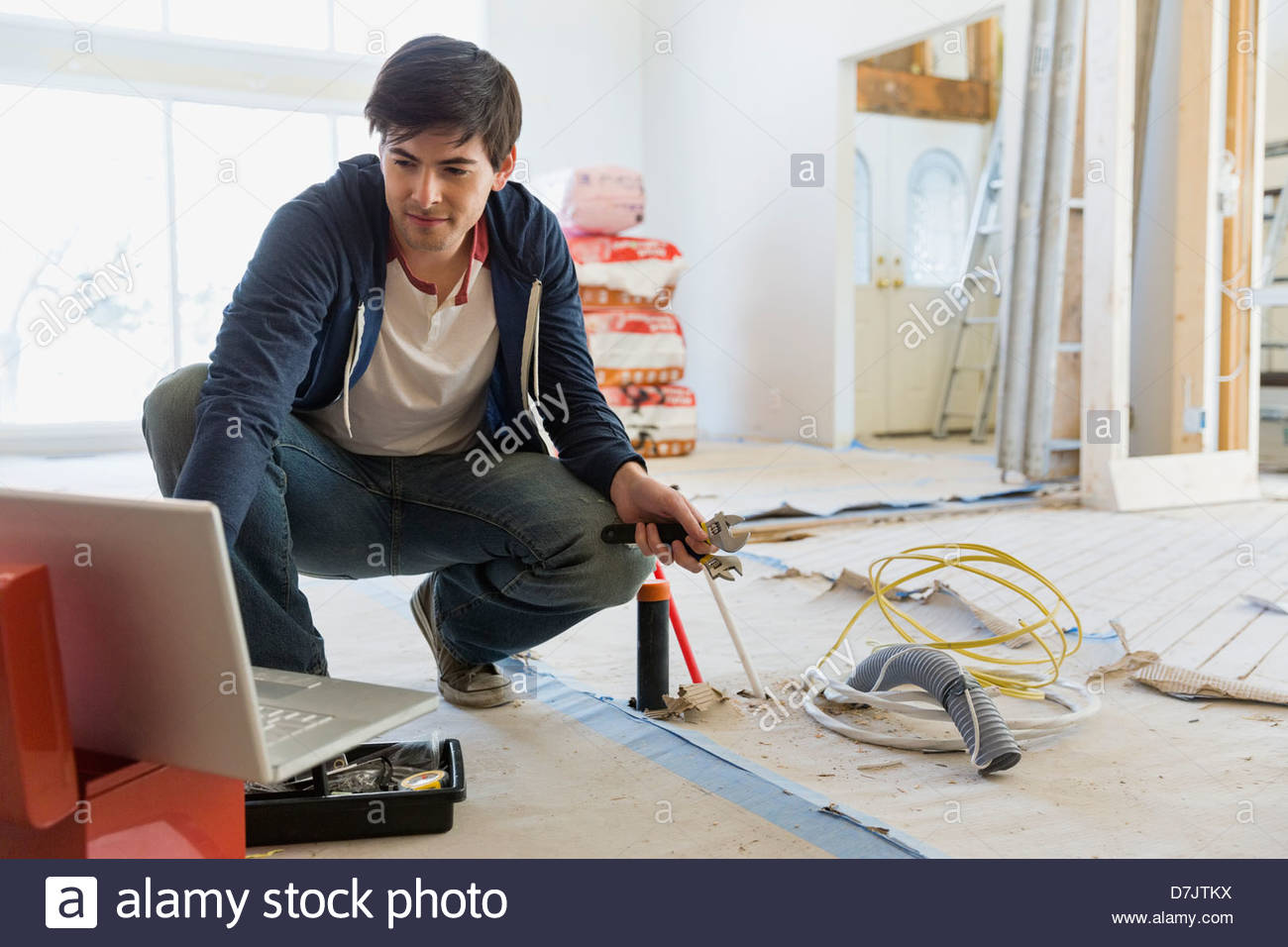 Young man consulting online advice for home renovations - Stock Image
