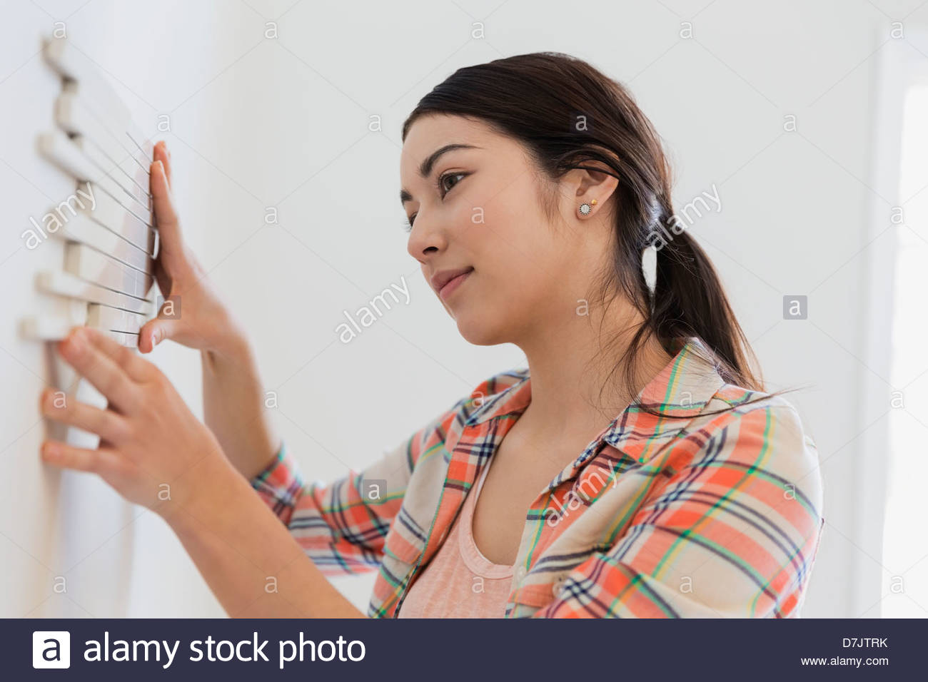 Young woman decorating wall with tiles at home - Stock Image