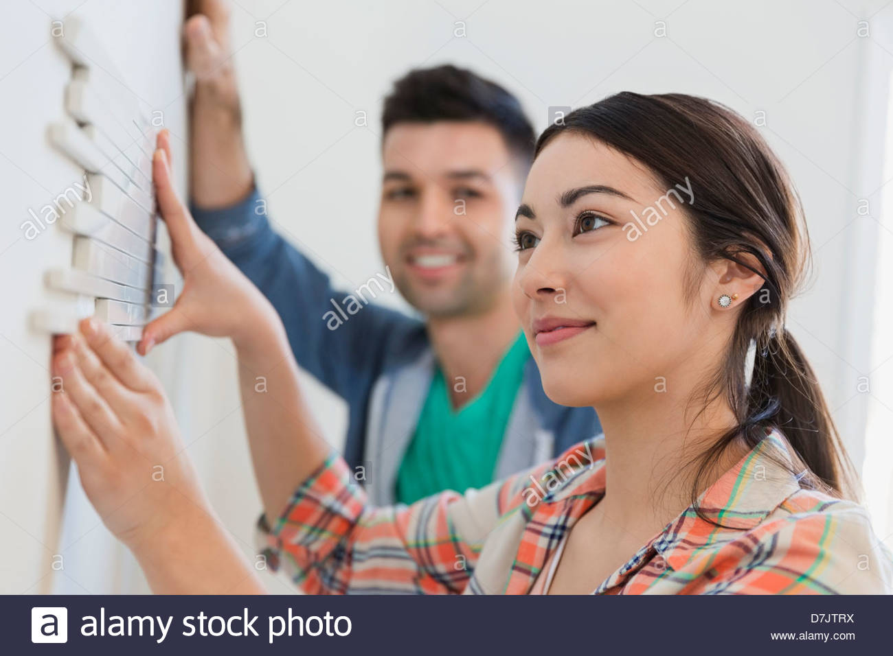 Young couple decorating wall with tiles at home - Stock Image