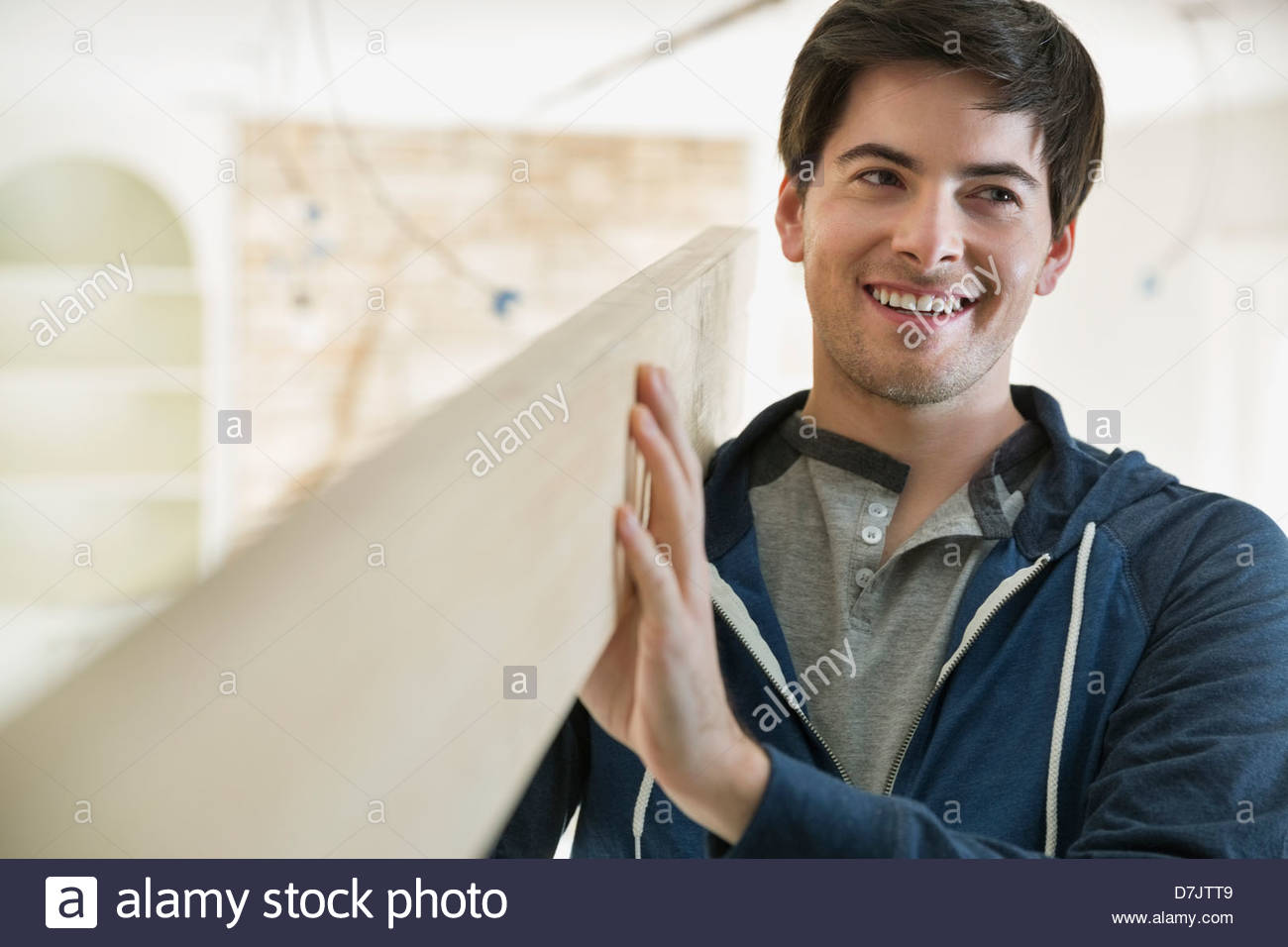 Smiling young man carrying lumber at home - Stock Image
