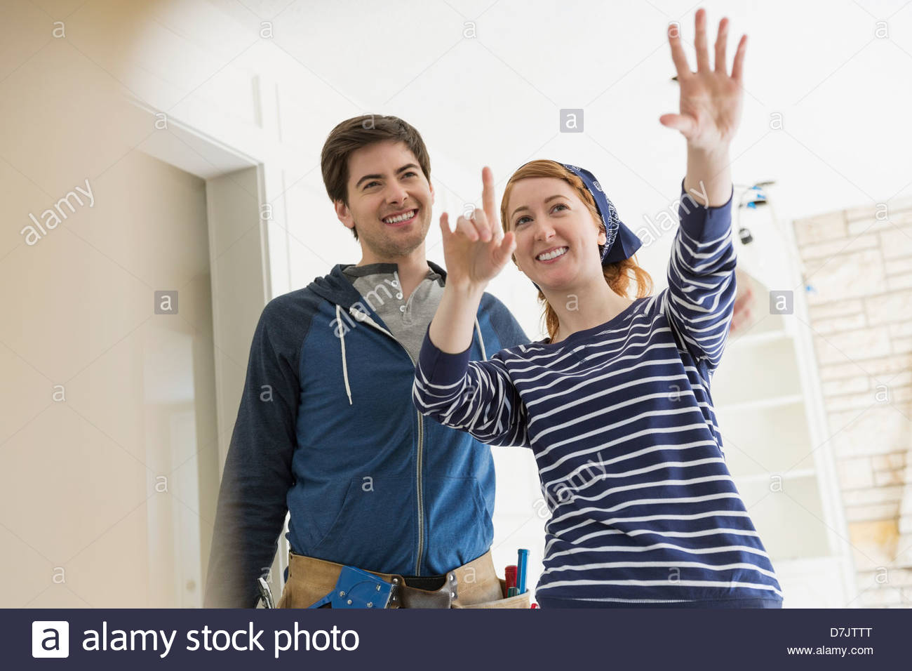 Smiling young couple discussing renovations at home - Stock Image