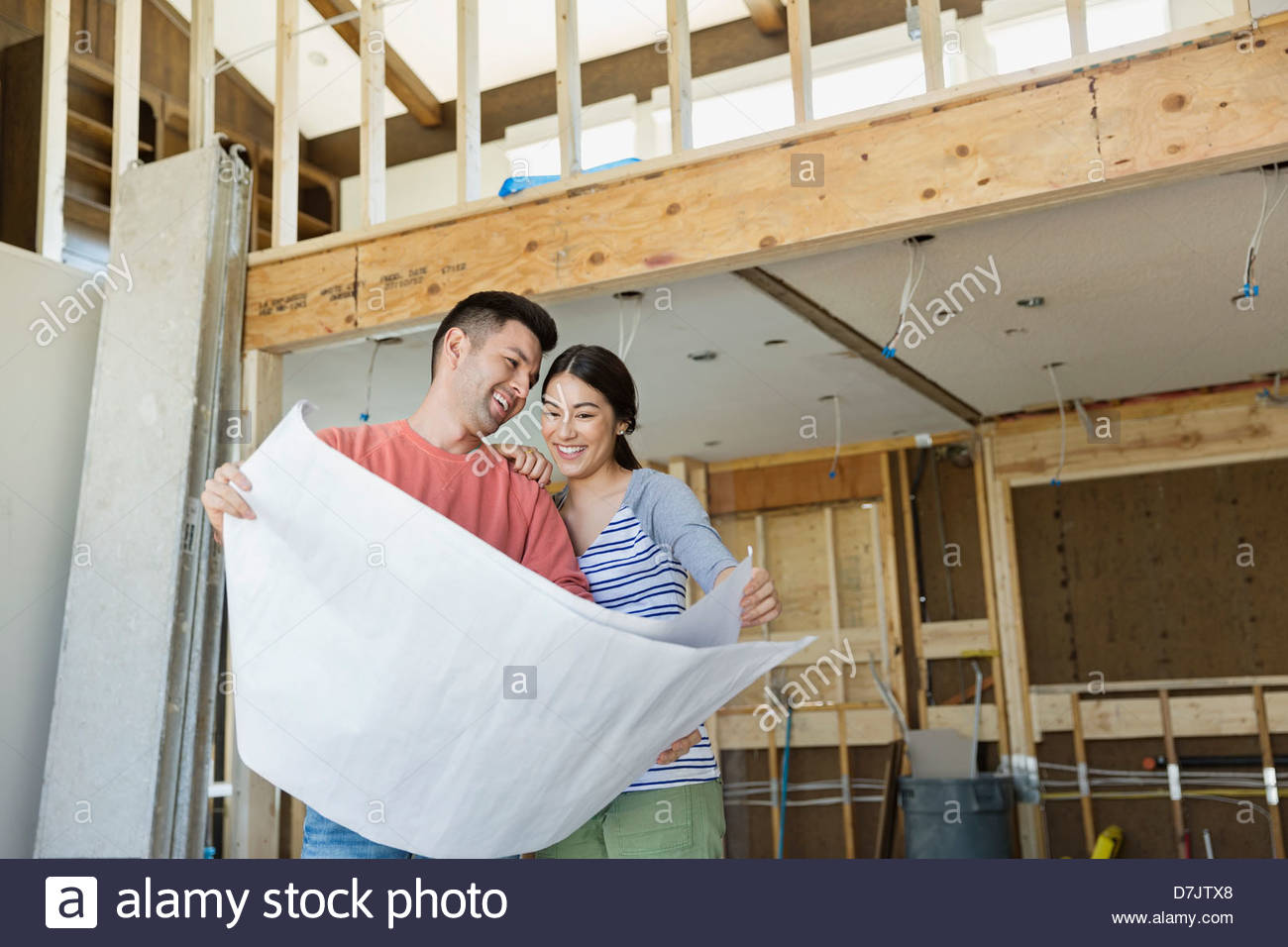 Smiling young couple checking blueprints at home - Stock Image