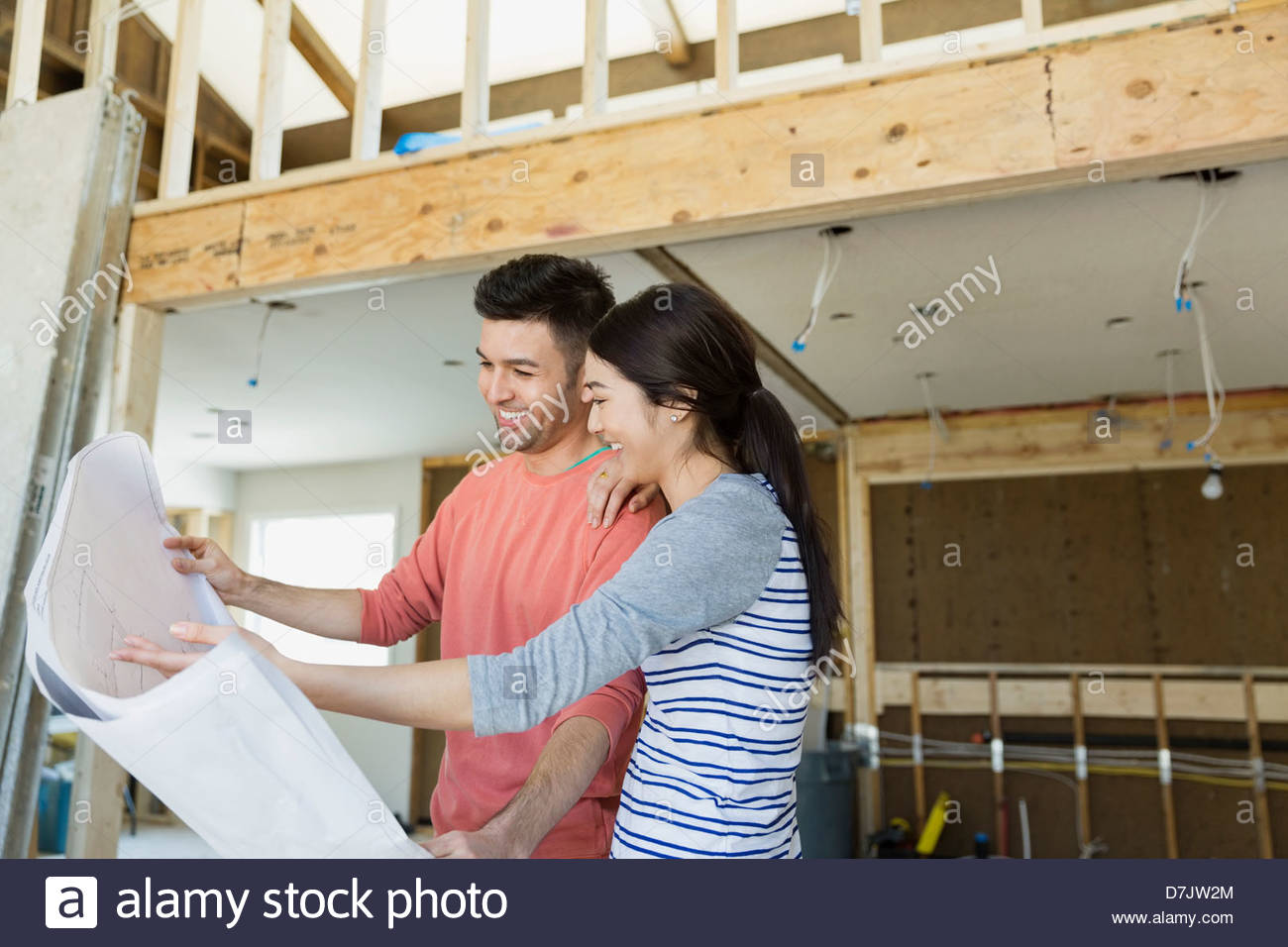 Young couple checking blueprints at home - Stock Image