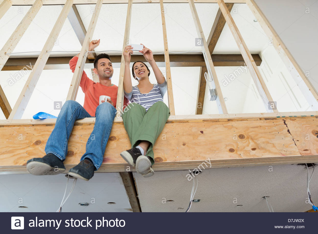 Young couple photographing home renovations - Stock Image