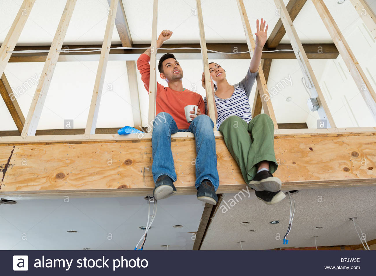 Young couple discussing renovations while taking coffee break - Stock Image