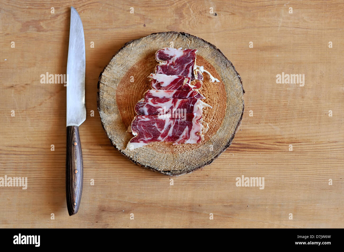 Slices of cured spanish jamon on a wooden cutting board Stock Photo