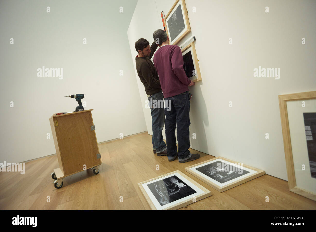 Staff at the Royal Albert Memorial Museum in Exeter England Hanging 'The Tannery' photography Exhibition. - Stock Image