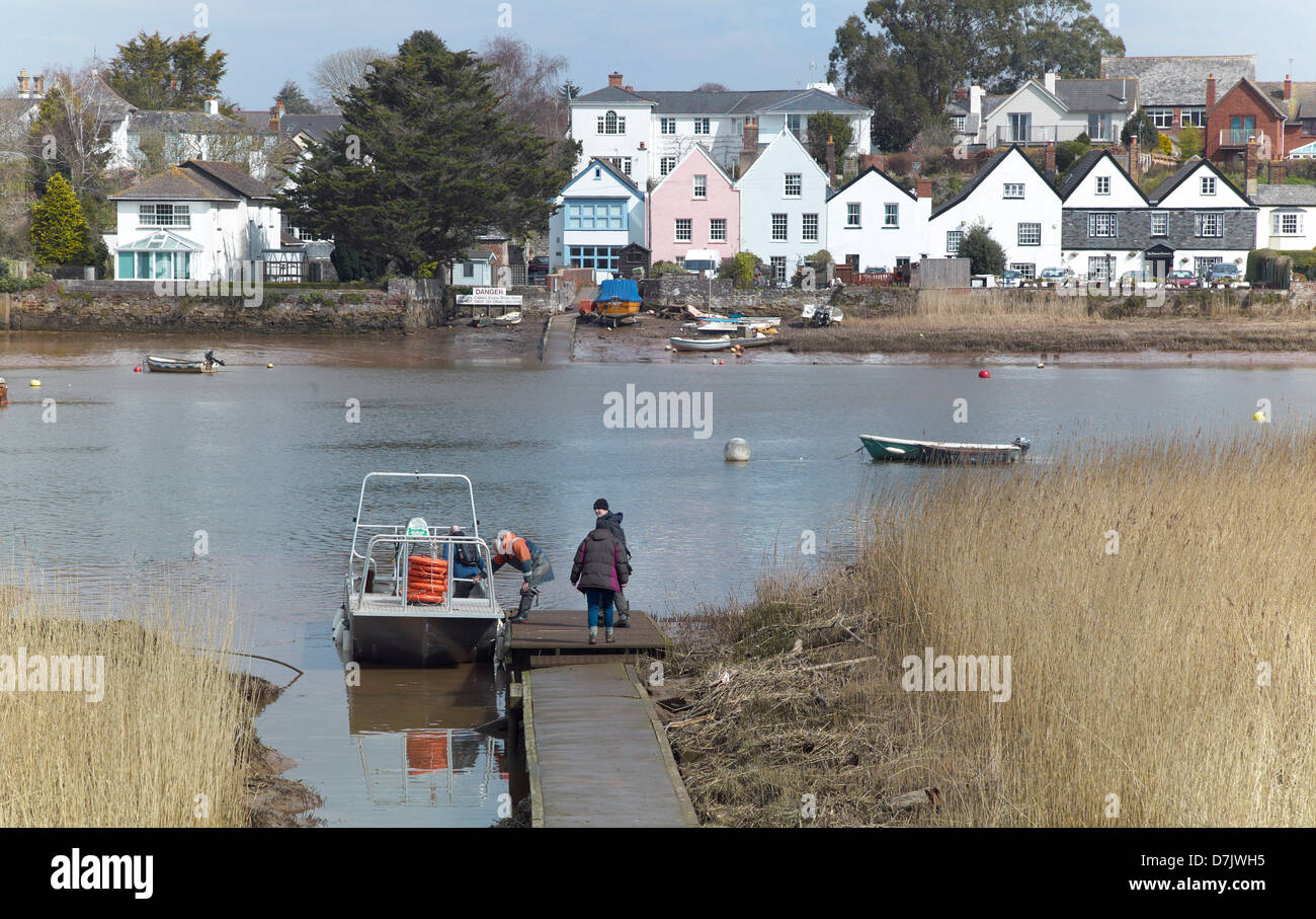 Passengers boarding the Topsham ferry on the banks of the river Exe with the village of Topsham, Devon, England, - Stock Image