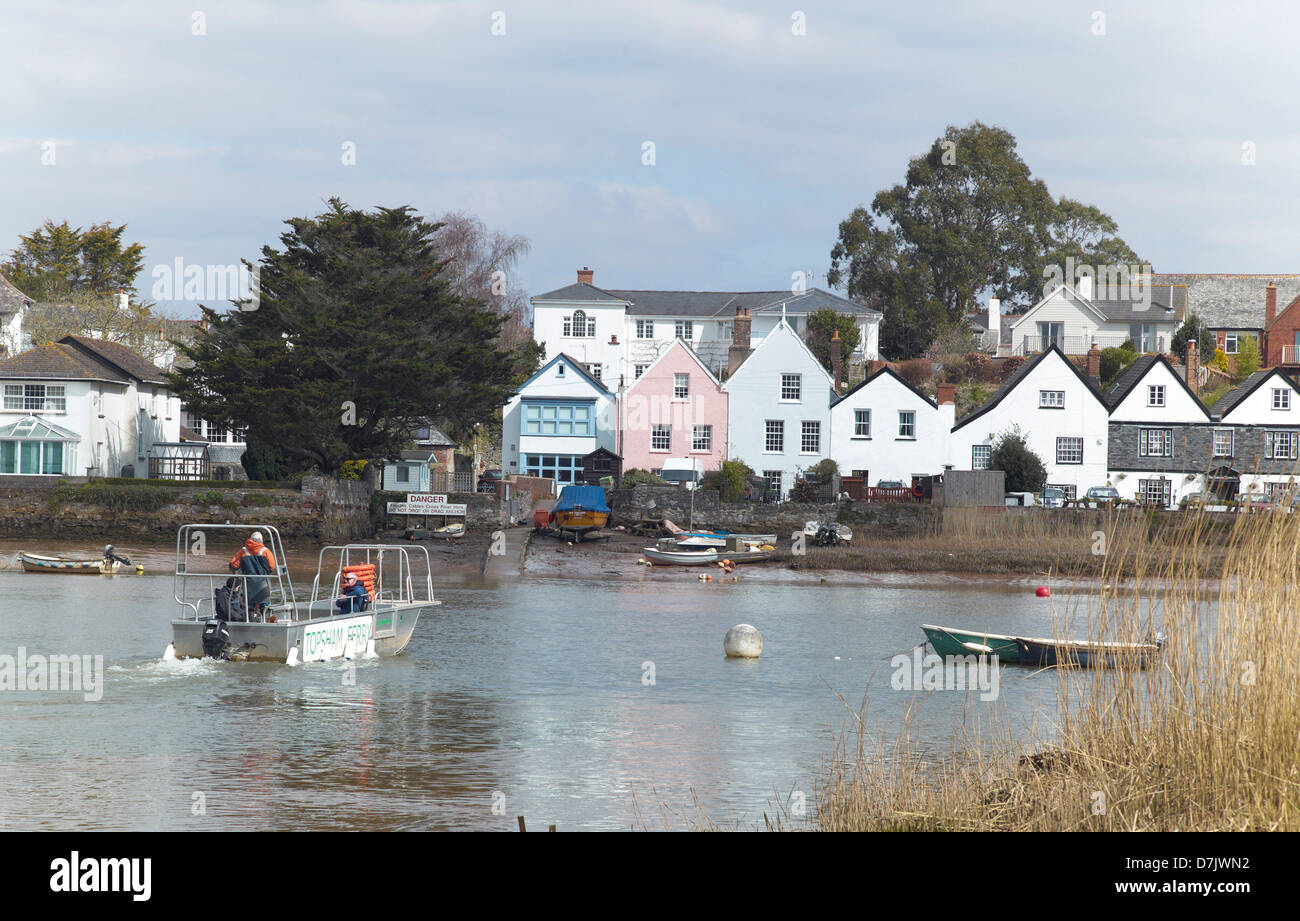 Passengers on the Topsham ferry on the banks of the river Exe with the village of Topshom, Devon, England, behind. - Stock Image