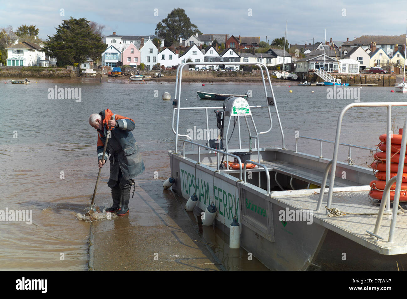 Ferryman cleaning the slipway of the Topsham ferry river exe exeter england - Stock Image