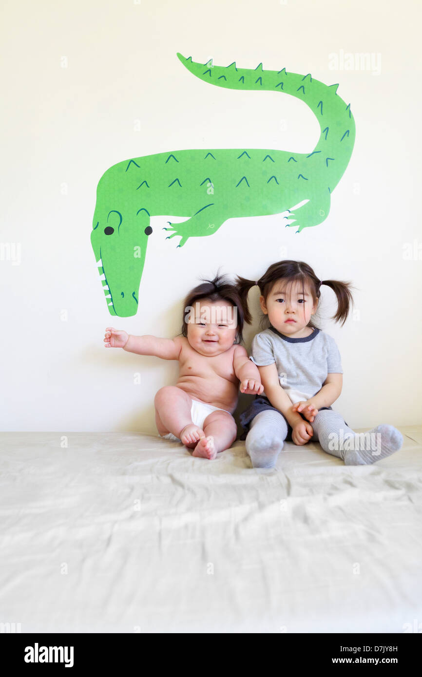 Two cute Korean American kids sitting on bed posing for camera in front of crocodile wall art - Stock Image