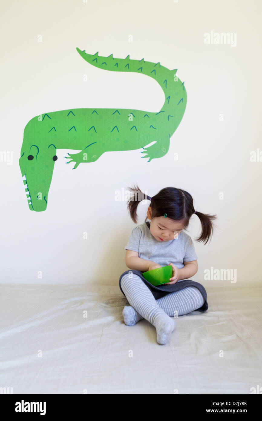 Korean American girl eating from green bowl with green crocodile wall art behind - Stock Image