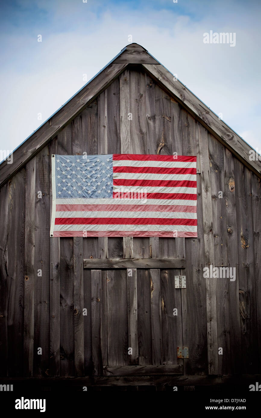 An old barn with US flag on it - Stock Image