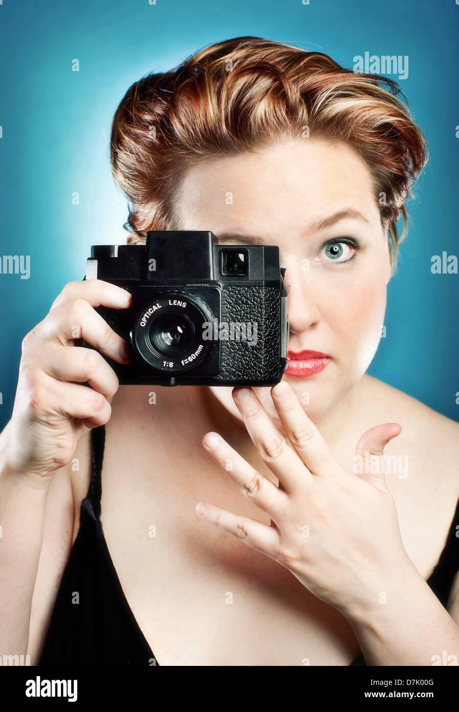 Portrait of young woman taking a picture with a toy camera in studio against blue backdrop - Stock Image