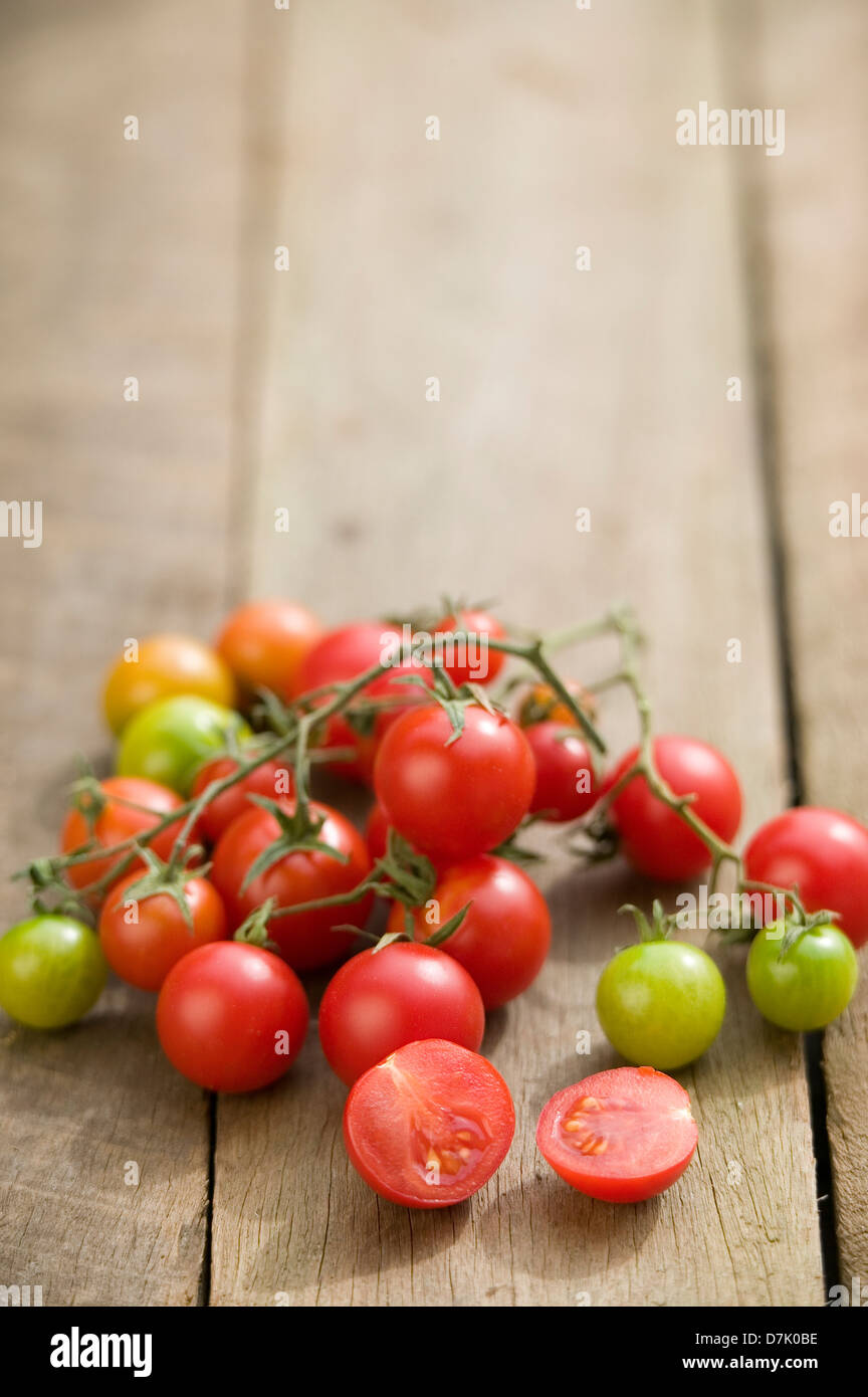Close up of a string of vine-ripe cherry tomatoes on a rustic wooden tabletop. - Stock Image
