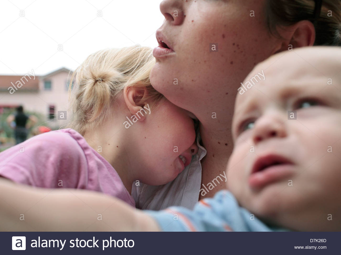 Young woman consoling her crying children - Stock Image