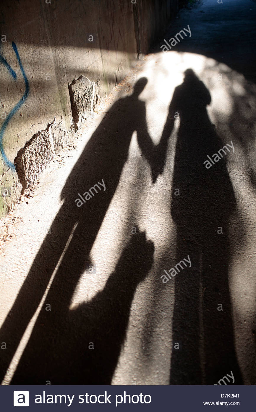 High angle view of shadow of a couple with a dog on the walkway Stock Photo