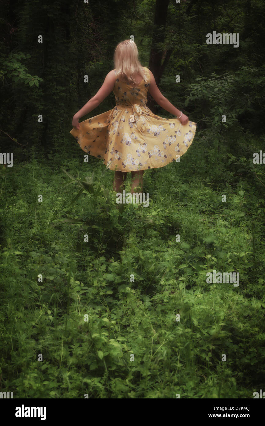 a blond girl with a yellow dress is dancing in the woods Stock Photo