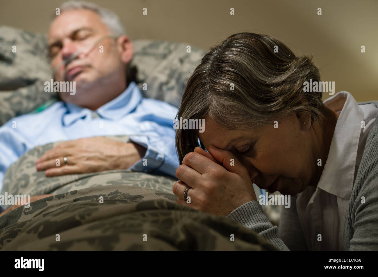 Senior woman praying for sick man sleeping in hospital bed - Stock Image