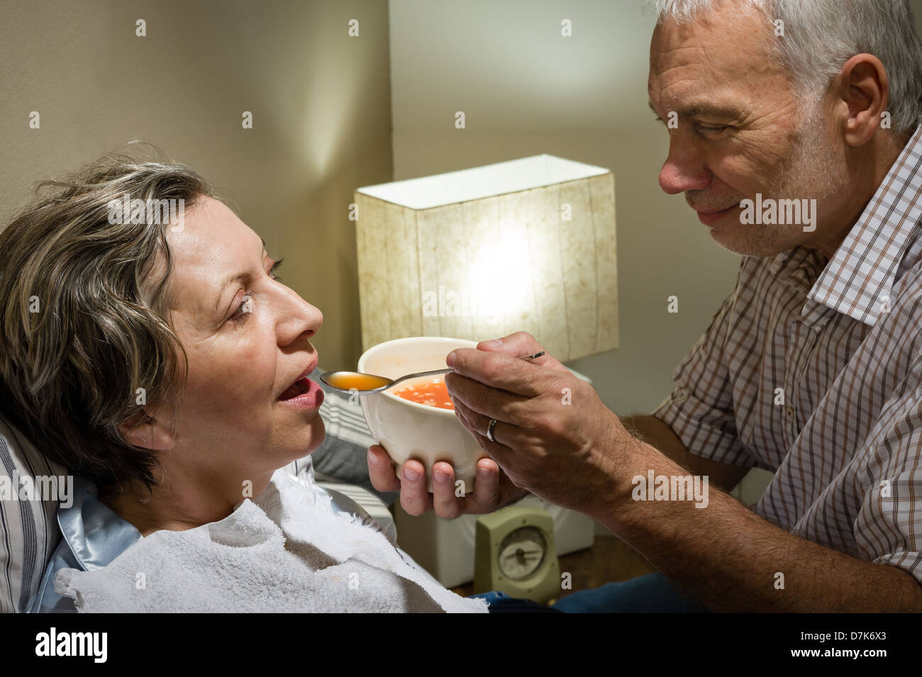 Loving retired husband feeding his ill wife with soup - Stock Image