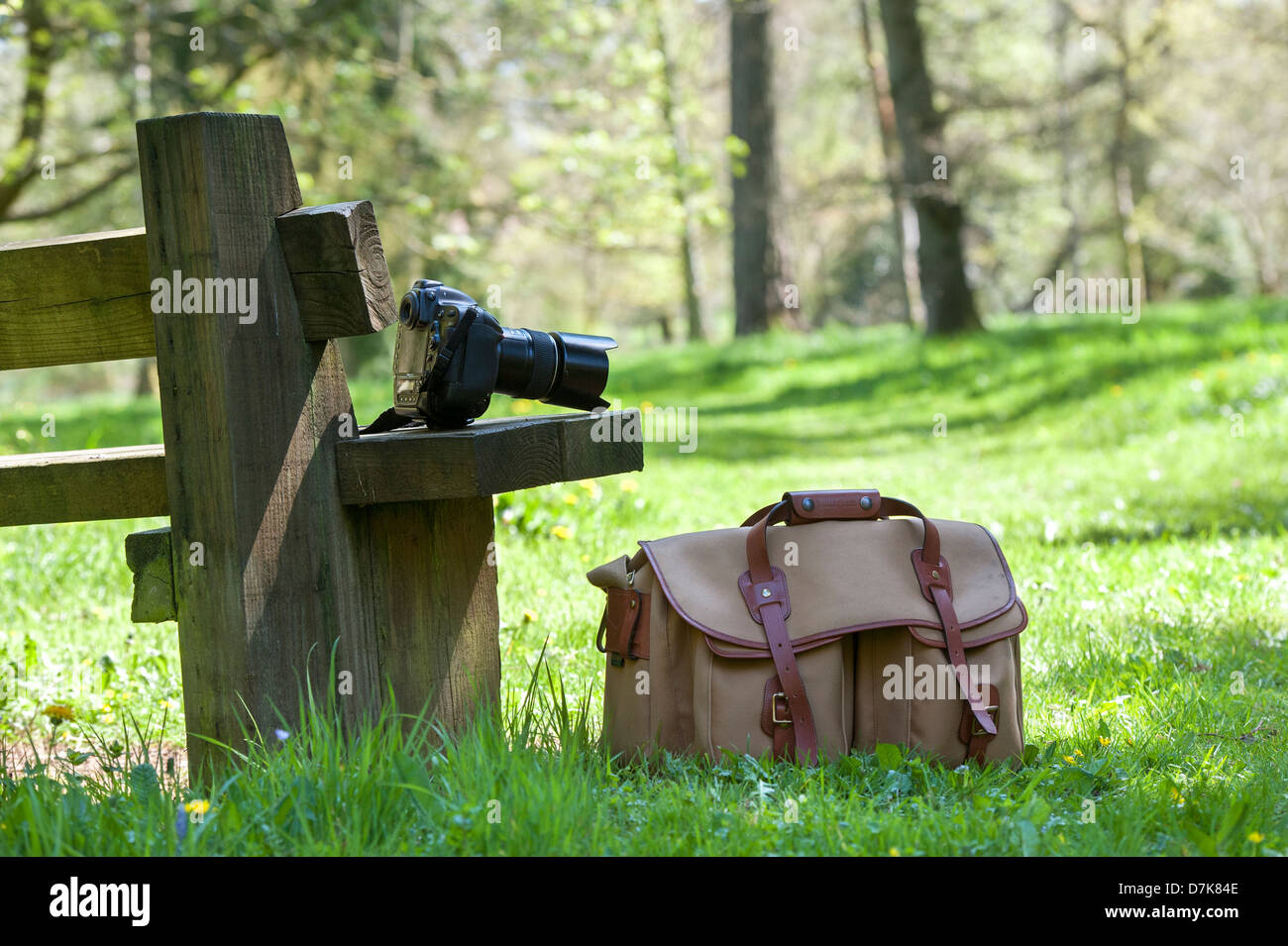 Nikon Camera equipment and bag on a seat in an English woodland - Stock Image