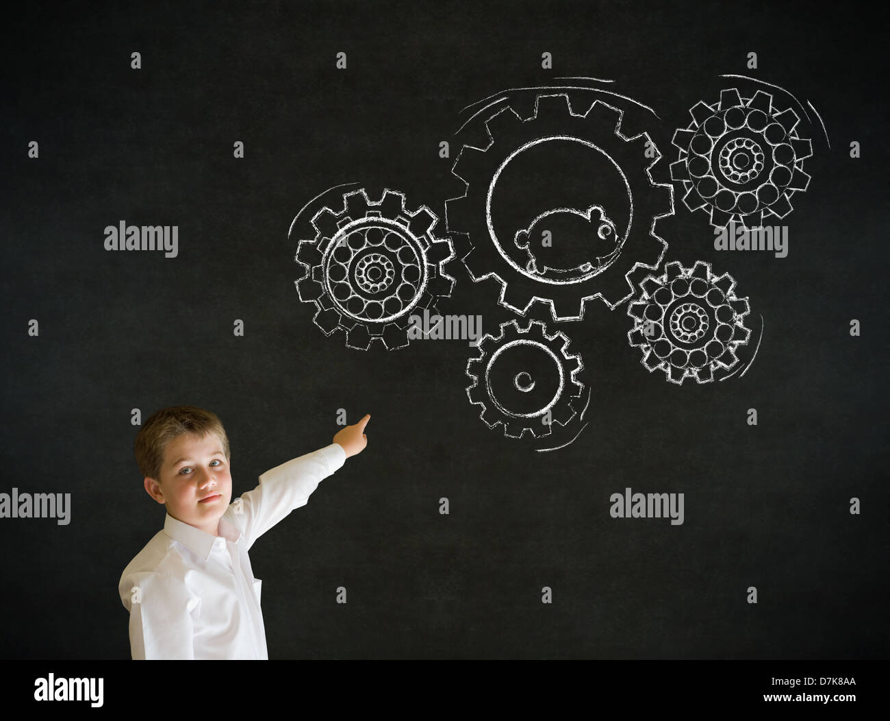 Pointing boy dressed up as business man with chalk turning gear cogs and running hamster on blackboard background - Stock Image