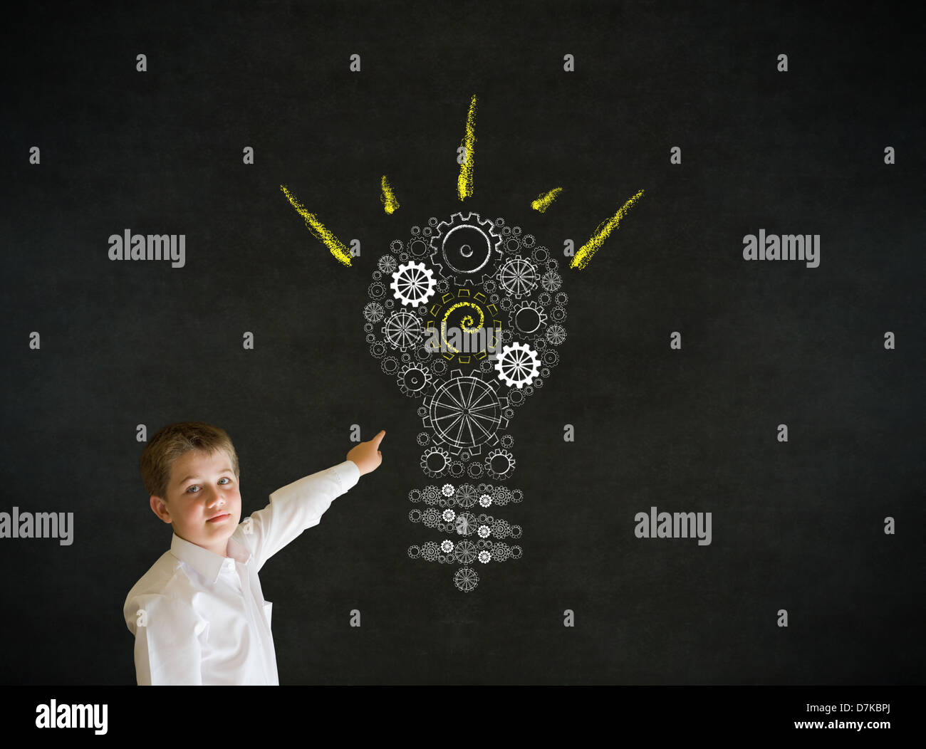 Pointing boy dressed up as business man with bright idea gear cog lightbulb on blackboard background - Stock Image