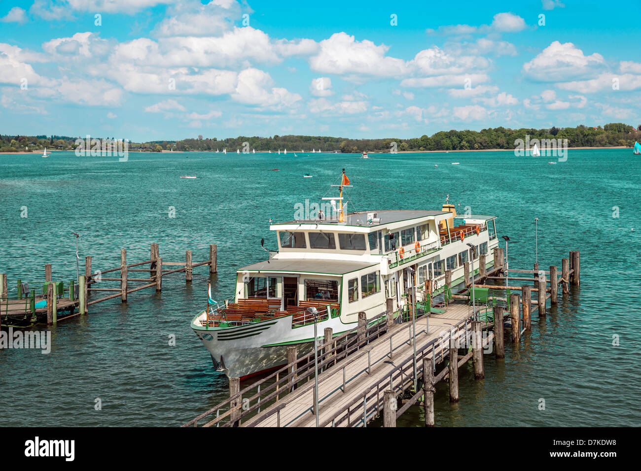 Passenger ship on lake Chiemsee in Germany with sailboat and bright sun. - Stock Image