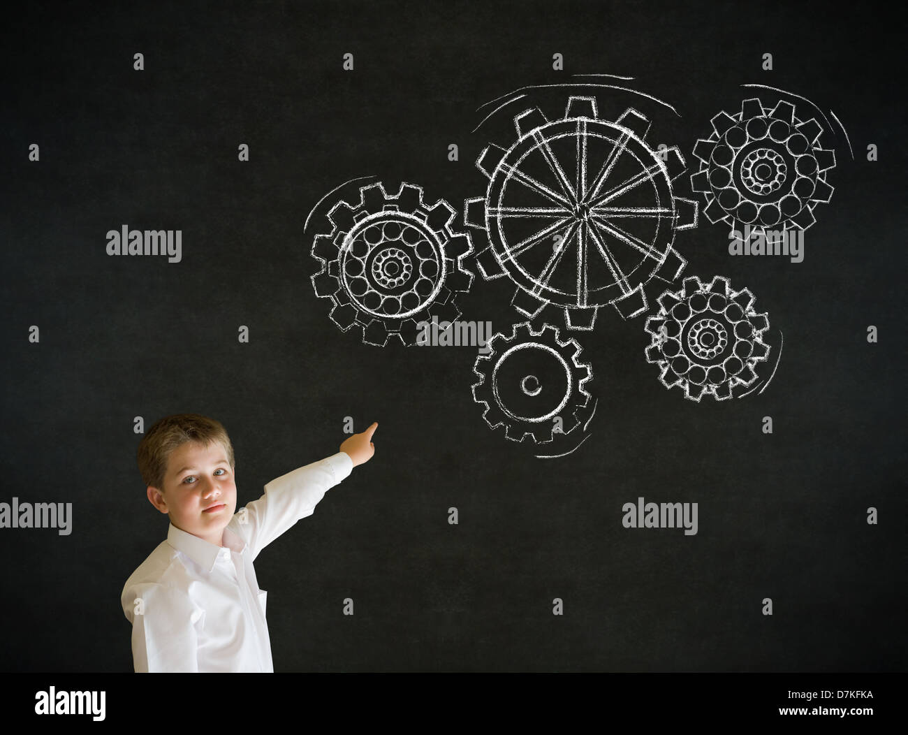 Pointing boy dressed up as business man with chalk turning gear cogs or gears on blackboard background - Stock Image