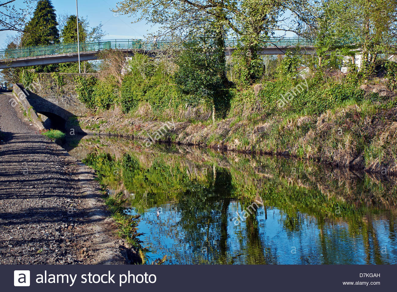 neath tennent canal and towpath under a stone bridge and footbridge - Stock Image