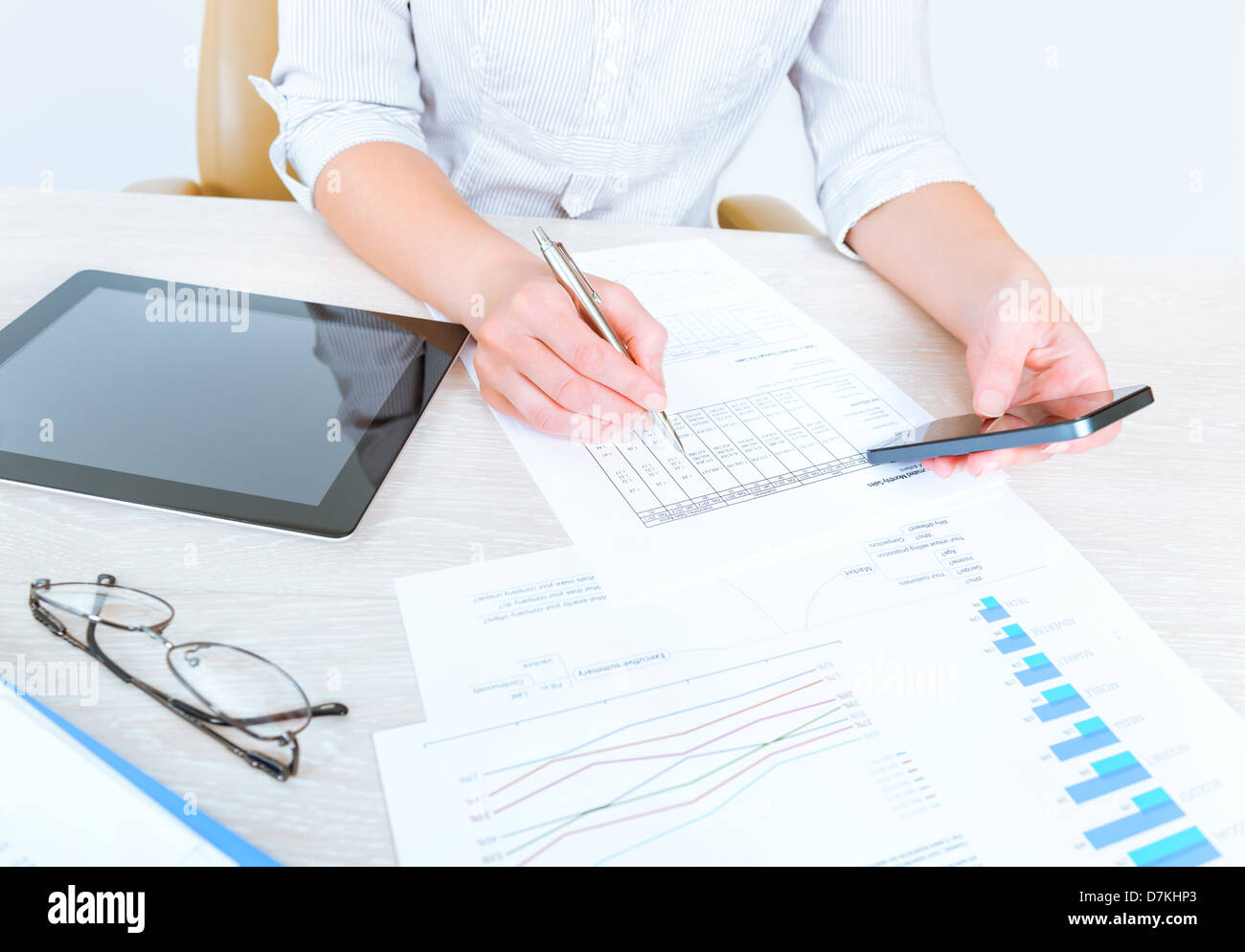 Successful businesswoman sitting at desk in casual clothes and using modern devices for analyzing sales statistics - Stock Image