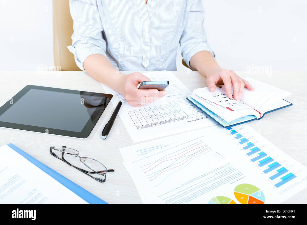Successful businesswoman sitting at desk in casual clothes and planning her working day in the office - Stock Image