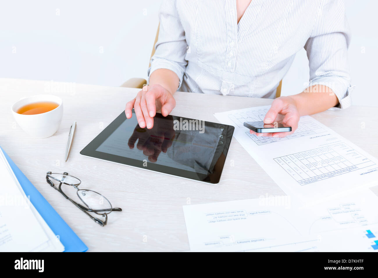 Successful businesswoman sitting at desk and simultaneously using modern devices for business communication - Stock Image