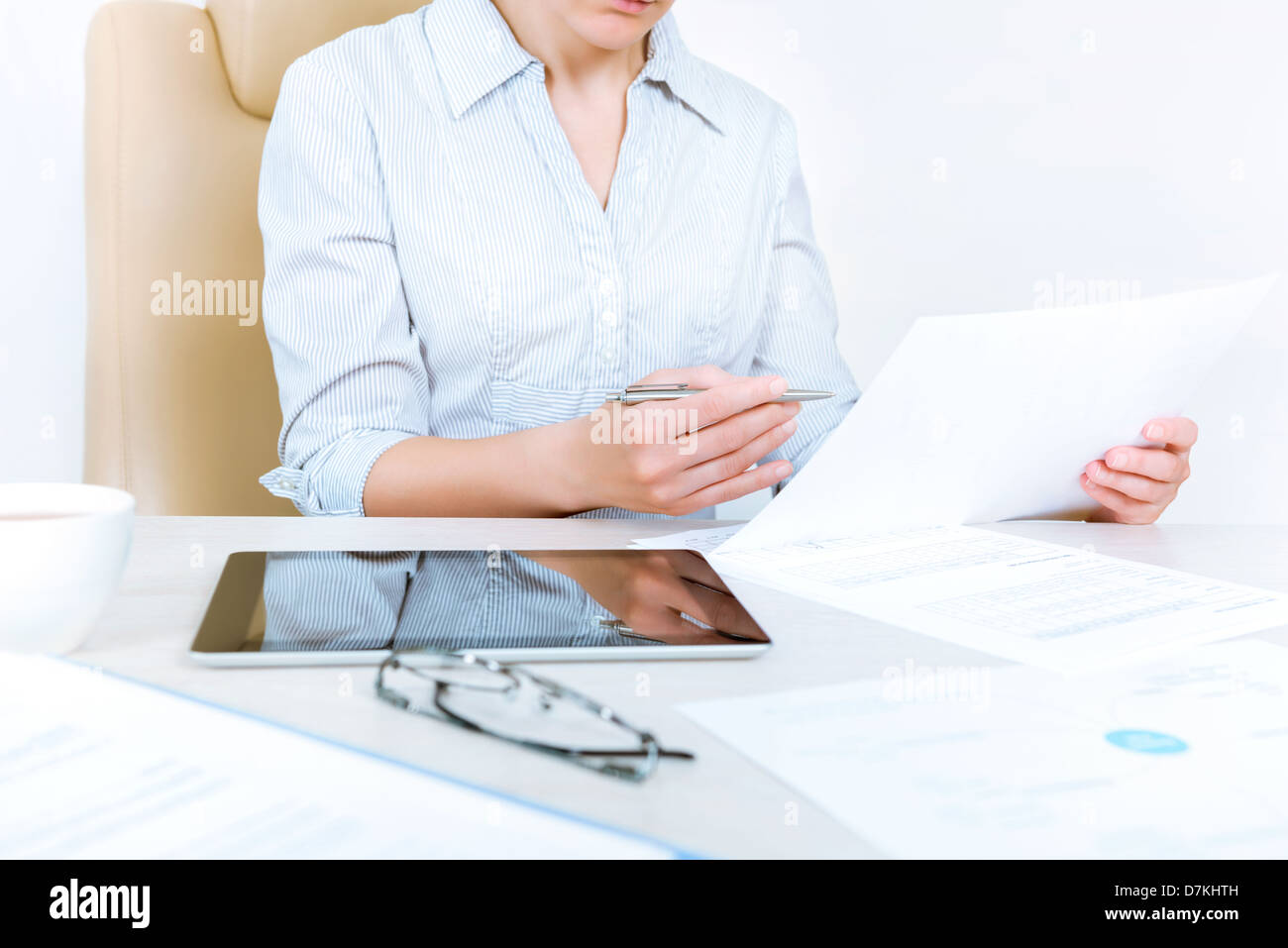 Busy businesswoman wearing in casual shirt sitting at desk and check documents in the office - Stock Image