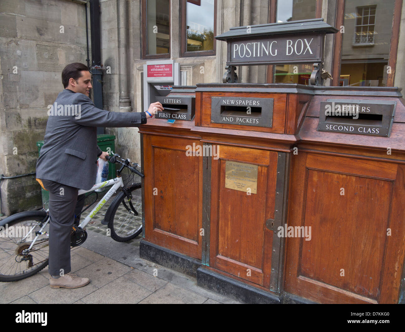 Man posting letter in an old fashioned Post Office in Oxford, England, UK - Stock Image