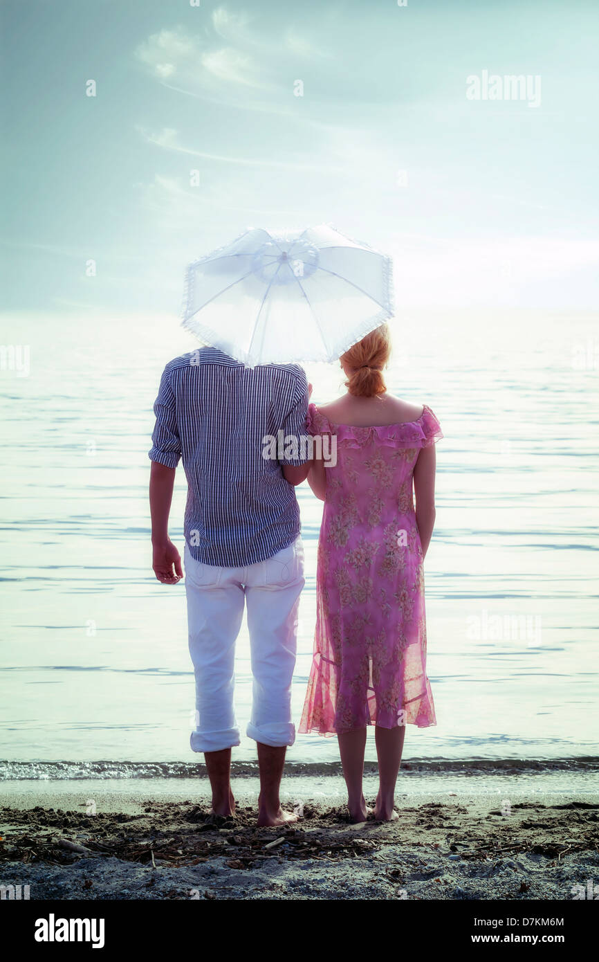 a couple on the beach with a parasol - Stock Image