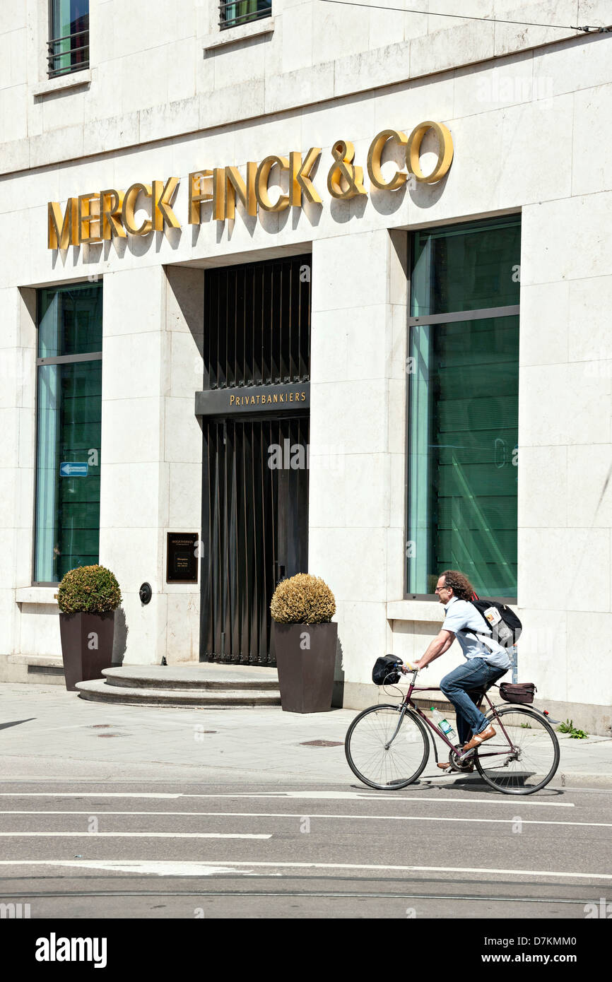 Man riding bike past Merck Finck & CO private bankers office building, Munich, Upper Bavaria Germany - Stock Image