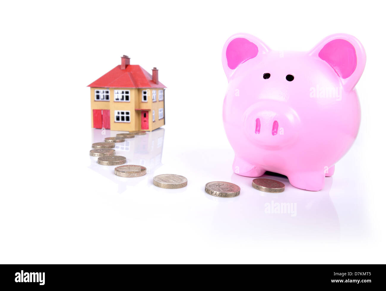 concept of mortgage piggy bank with a path of coins to a house - Stock Image