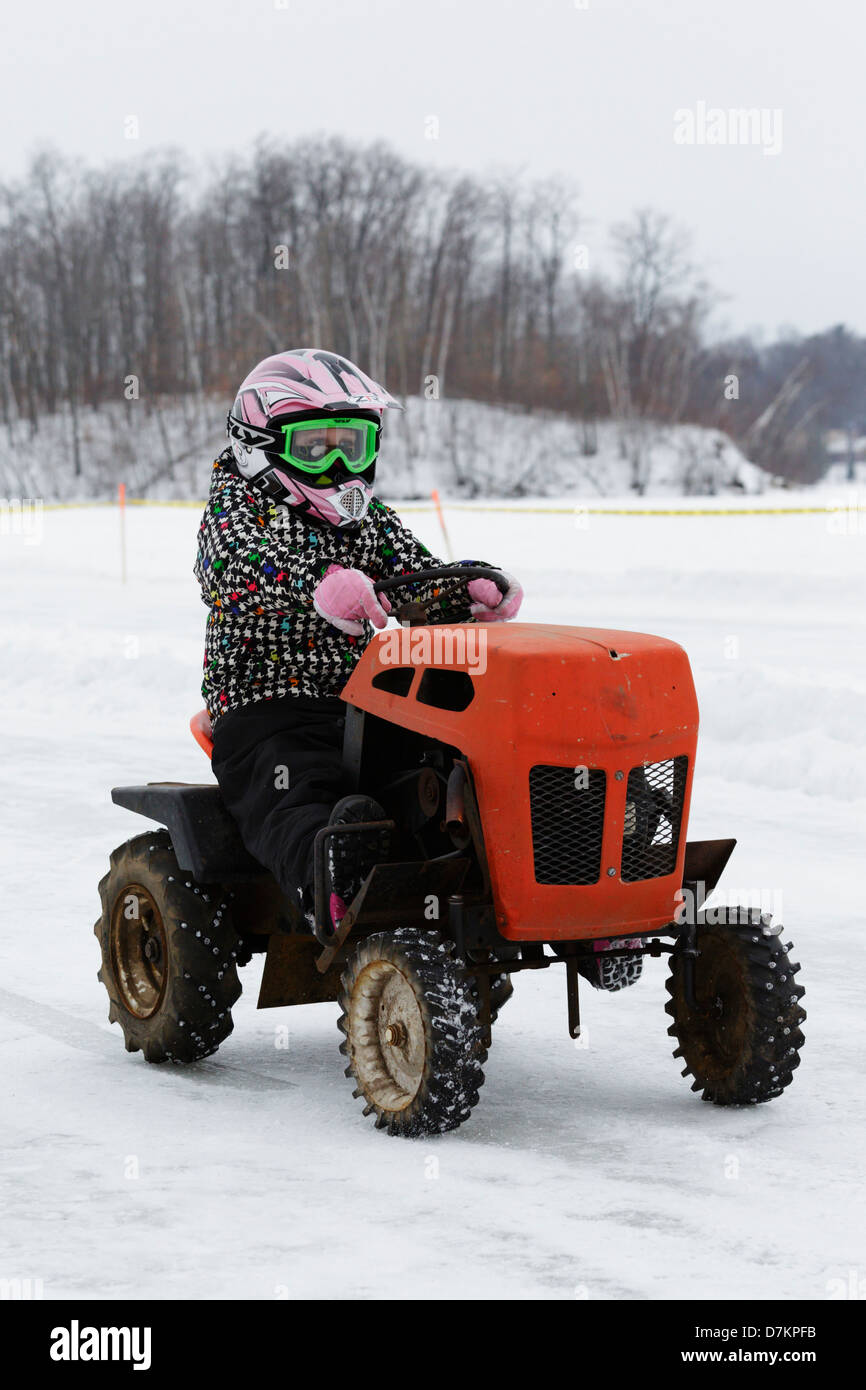 A youngster drives an old lawn mower during a pre-event parade before the first annual lawn mower ice races on Knife - Stock Image