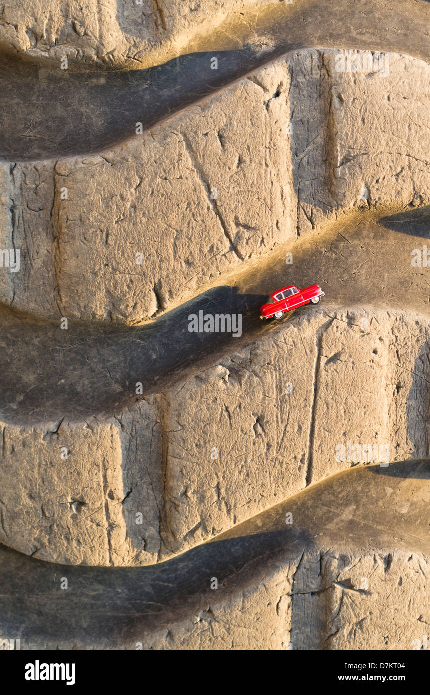 Small red toy car in tread of large truck tire - Stock Image