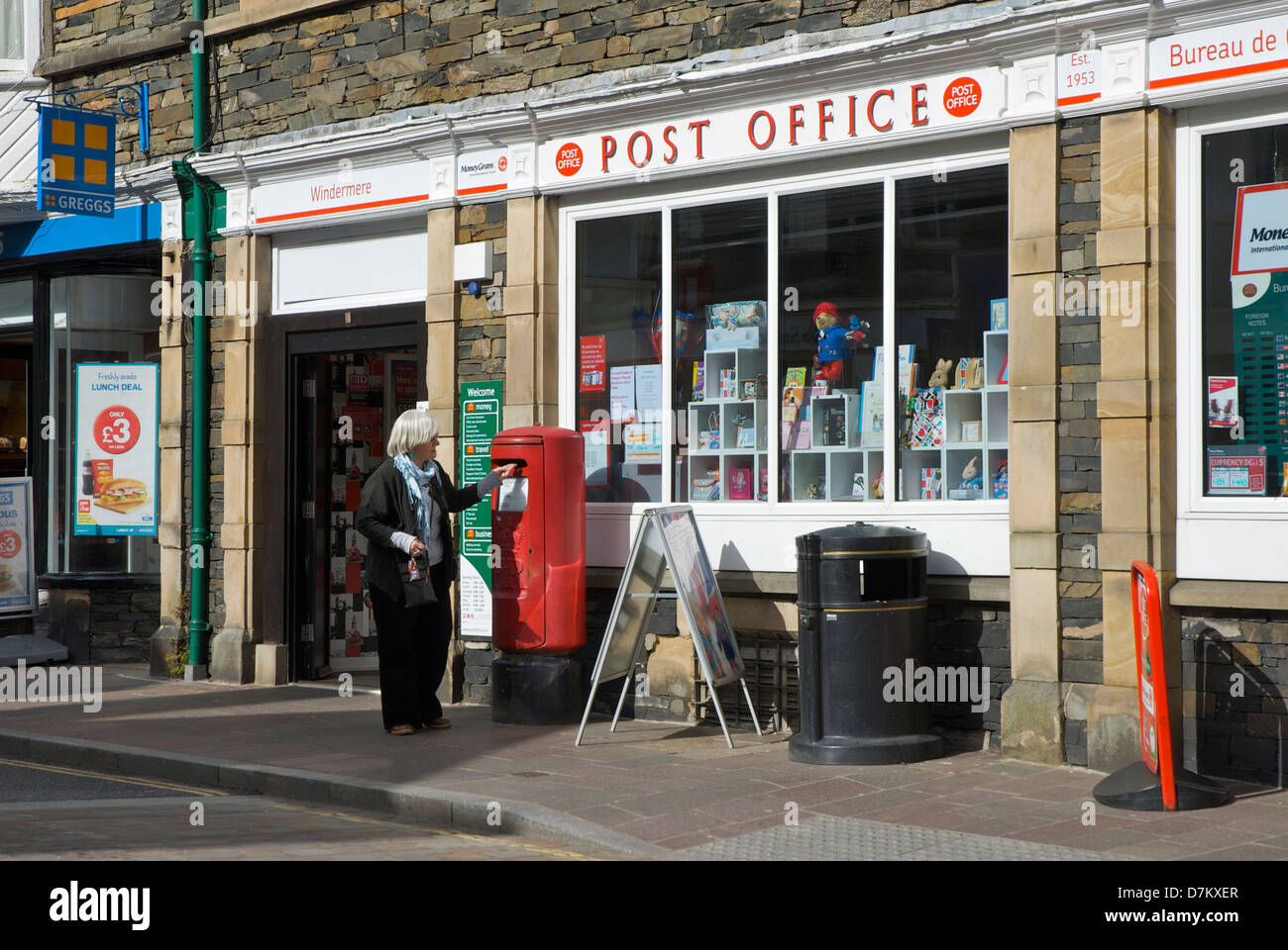 Middle-aged woman posting letter outside Windermere Post Office, Lake District National Park, Cumbria, England UK Stock Photo