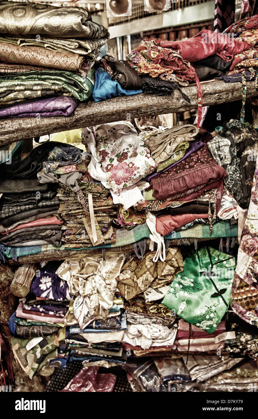 very rough pile of clothing on shop shelf in chinatown kl malaysia - Stock Image