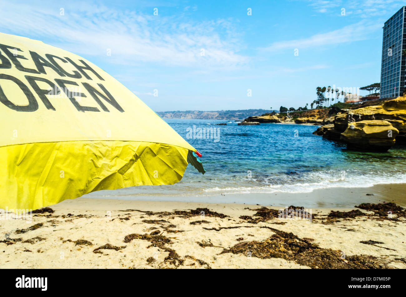 Children's Pool Beach. La Jolla, CA, USA. Beach Open sign written on a beach umbrella. - Stock Image