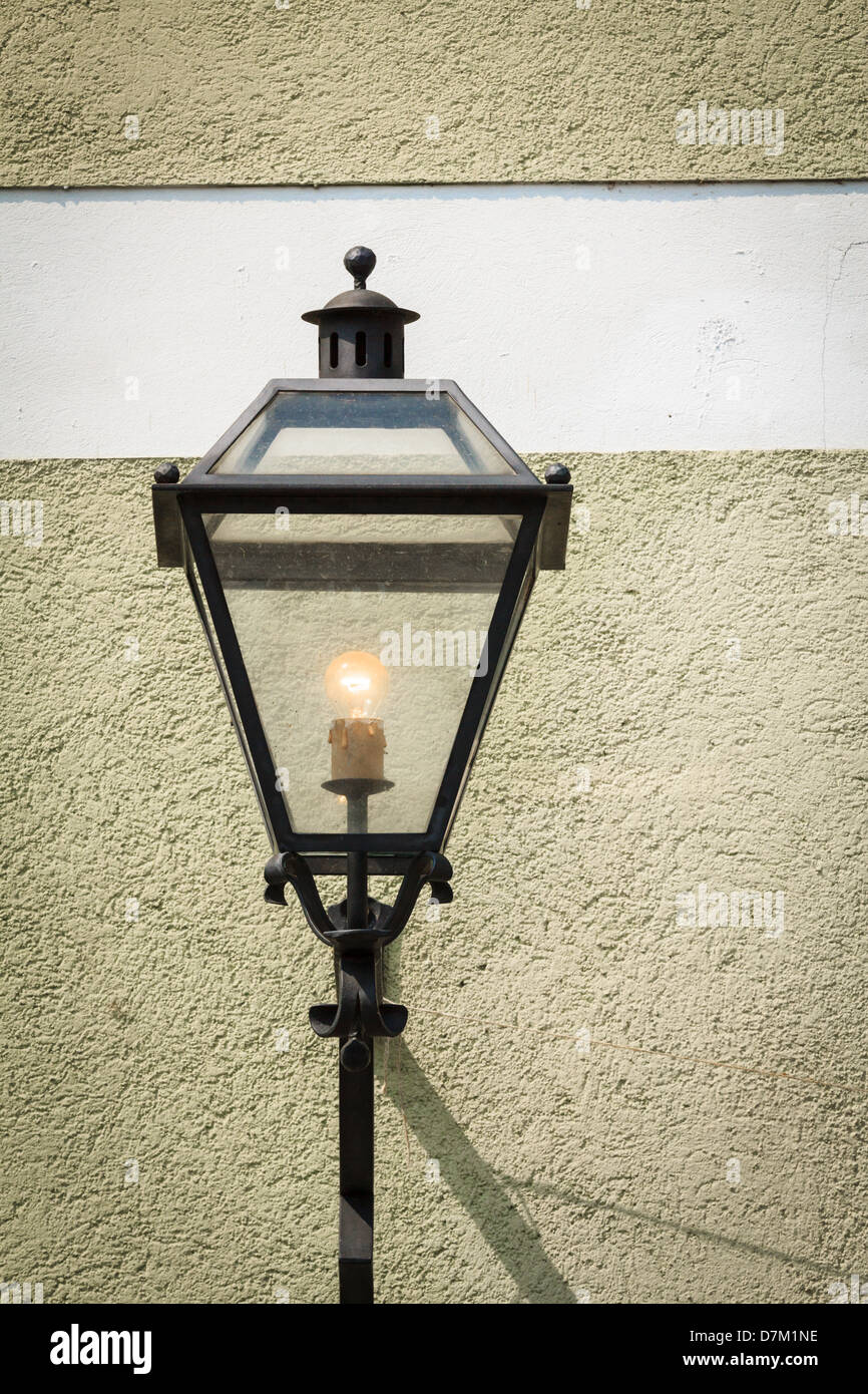 An old streetlamp next to a wall - Stock Image