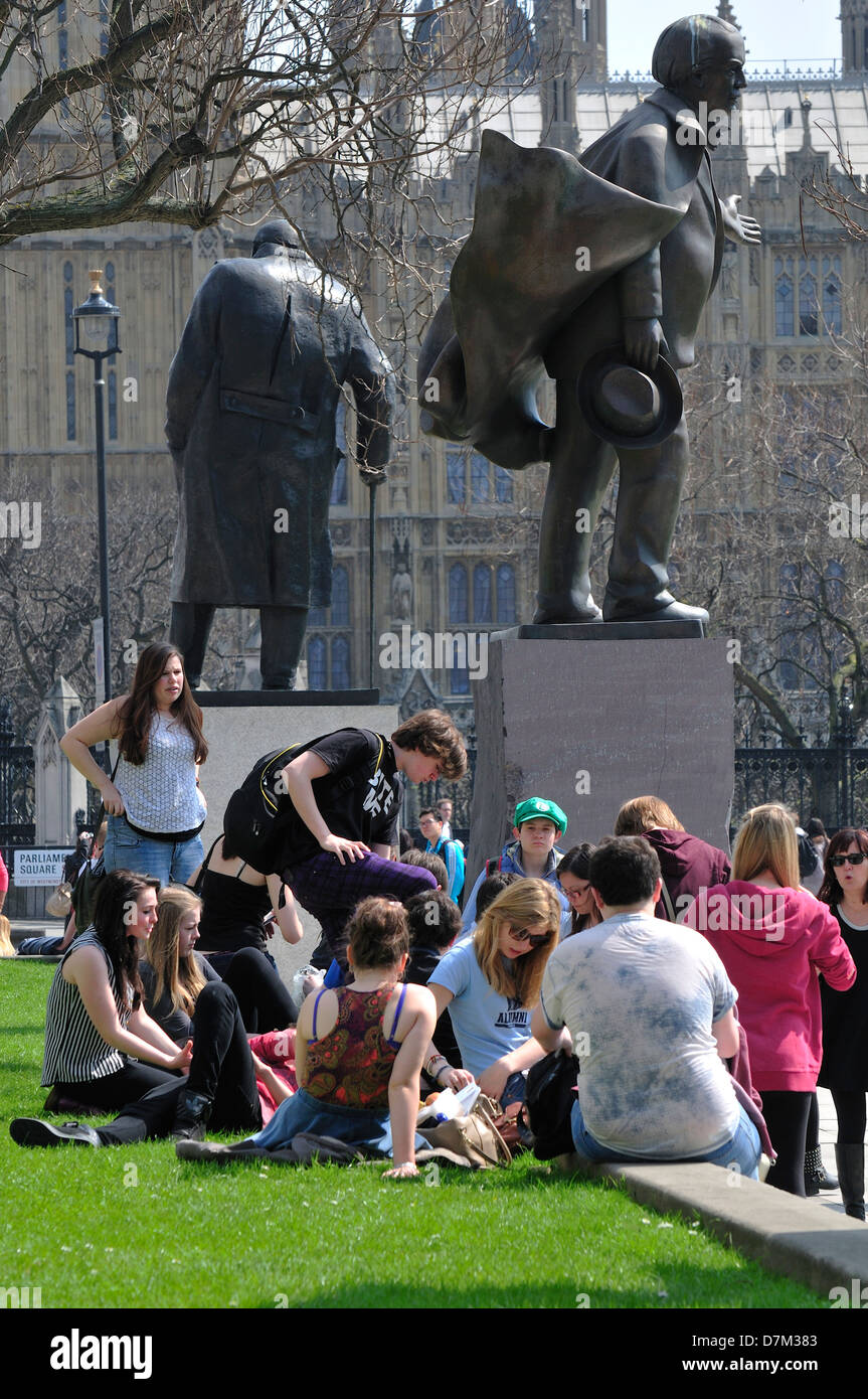 London, England, UK. People relaxing in Parliament Square - statues of Lloyd George and Churchill - Stock Image