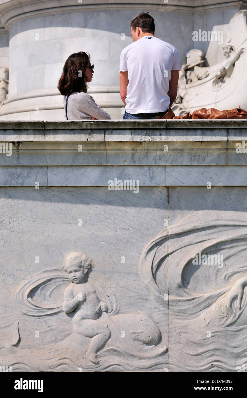 London, England, UK. Young couple at the base of the Victoria Memorial in front of Buckingham Palace - Stock Image