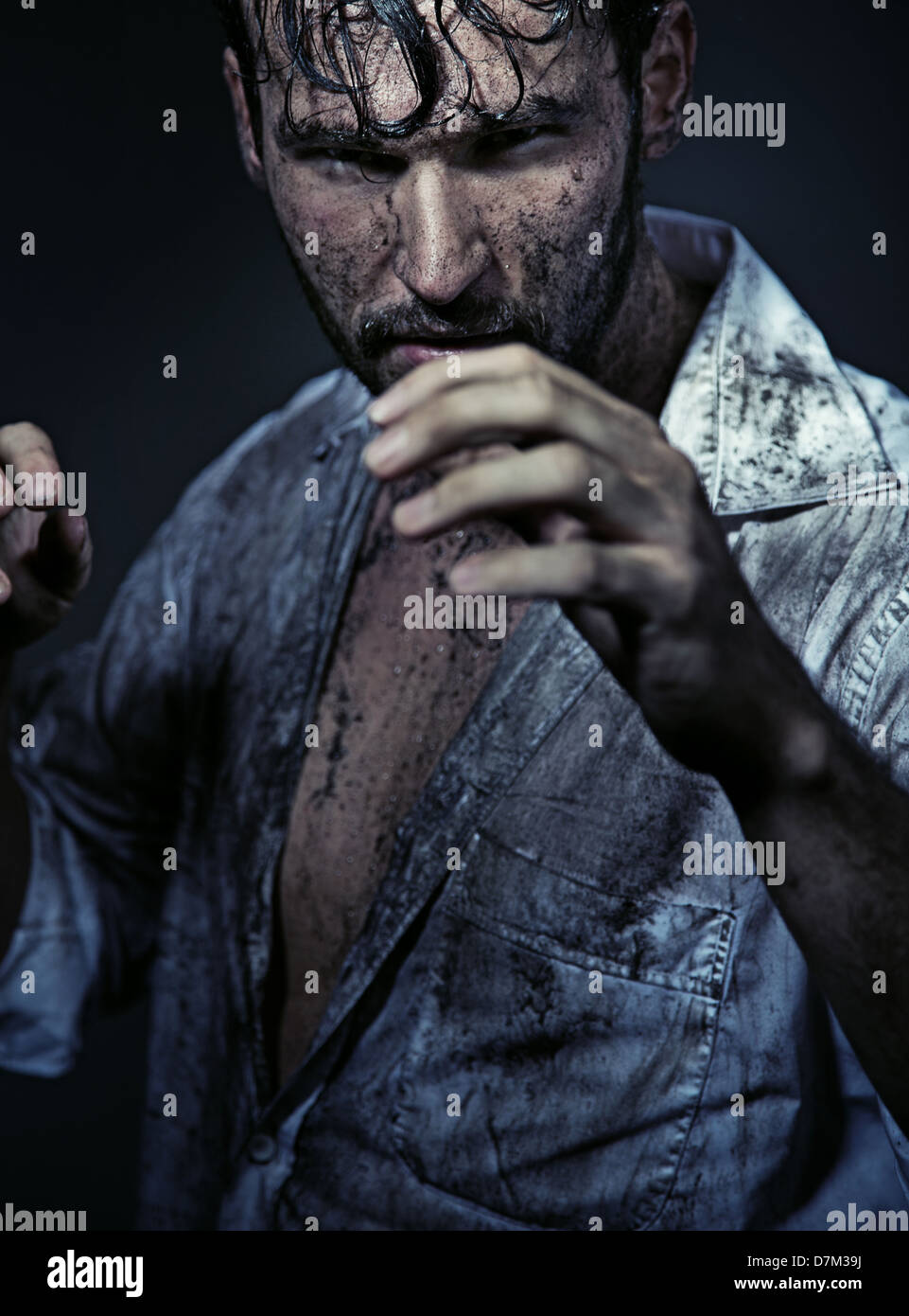 Dirty handsome guy prepareing to fight - Stock Image
