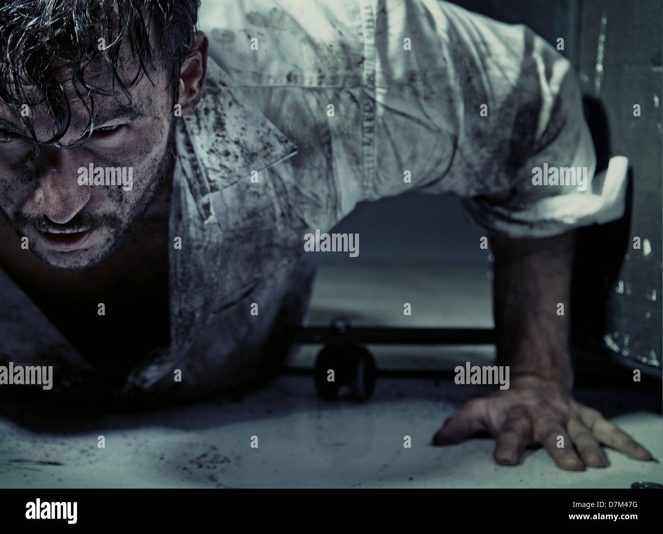 Dirty guy trying to get up - Stock Image