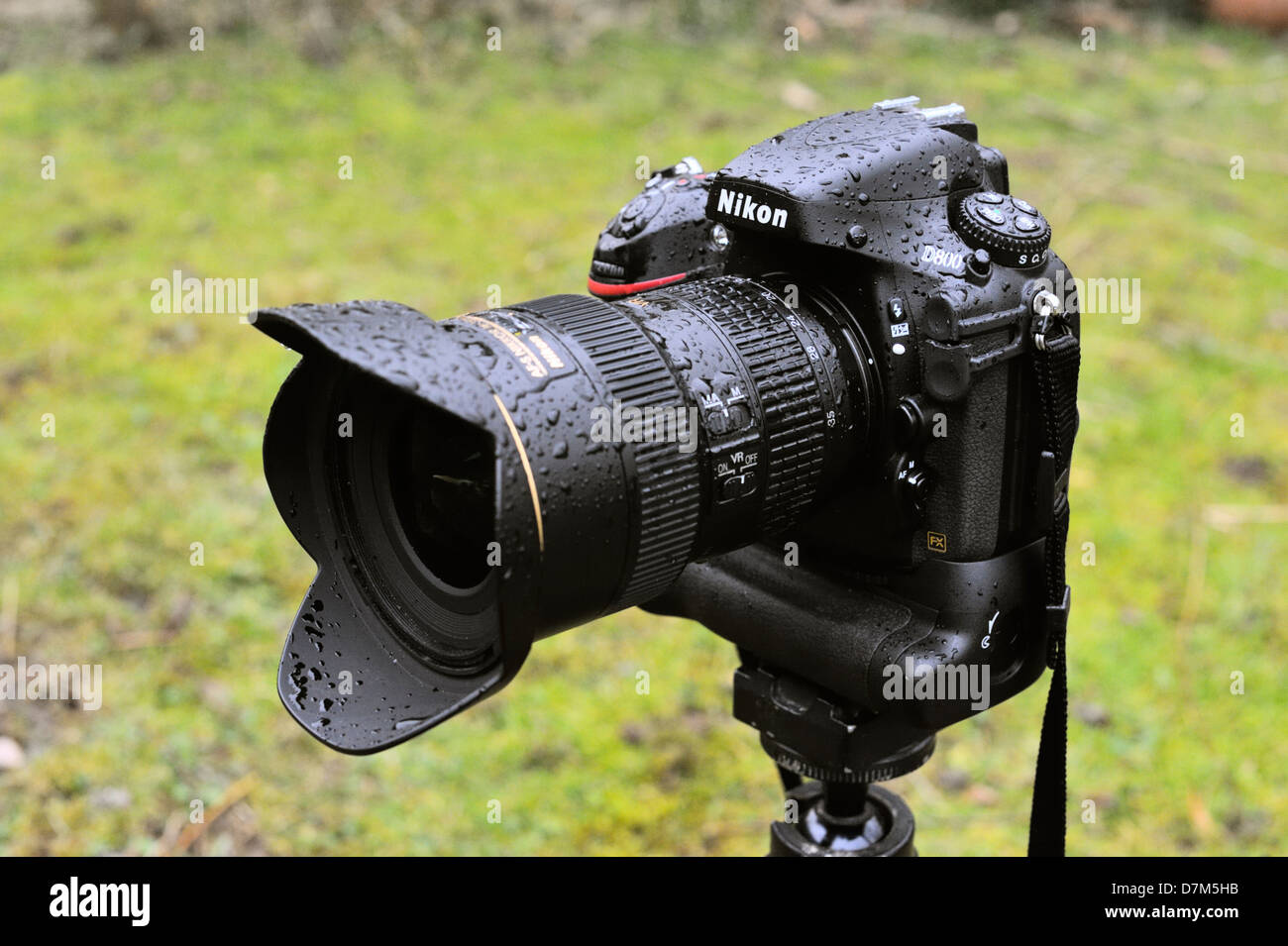Nikon D800 digital SLR camera with MBD-12 battery grip and 16-35 f4 VR lens attached, soaking wet after exposure - Stock Image