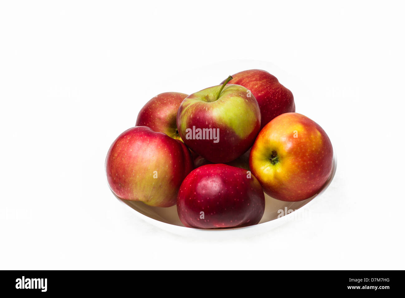 Isolated photo of red apples on a white plate - Stock Image
